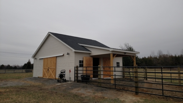 This barn is configured with (2) stalls on one side of center aisle with large open hay area and 6x12 tack room on other side of center aisle. 10' wide roll doors on both ends.